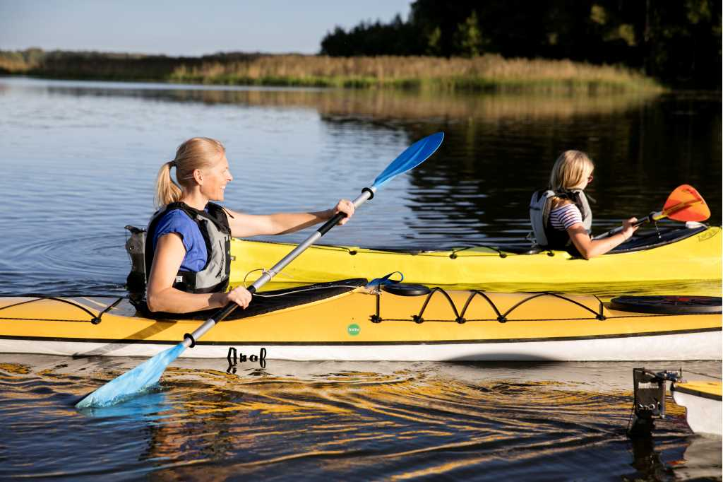 A fit looking woman and child are kayaking in yellow kayaks. The woman, seen in profile,  has a big smile on her face, while the young girl is looking away from the camera.