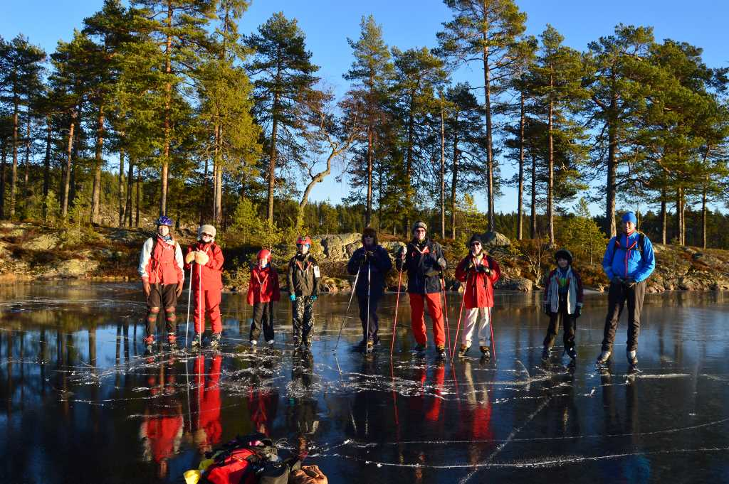 A group of people wearing ice skates are standing on a frozen lake