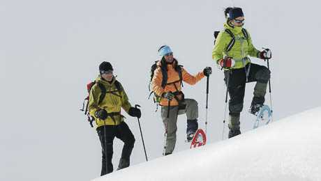 A group of people walking up a snowy hill wearing snow shoes