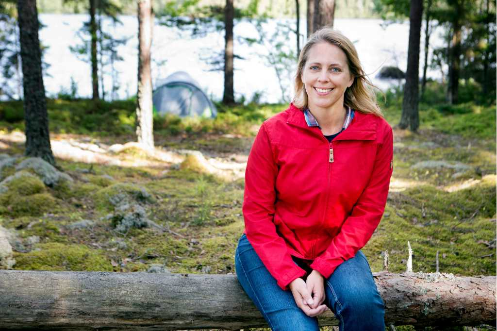 A woman is sitting on a log in the forest. She looks very happy.